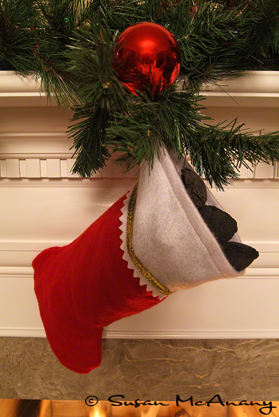 Stocking stuffed with coal with greenery and ornament.