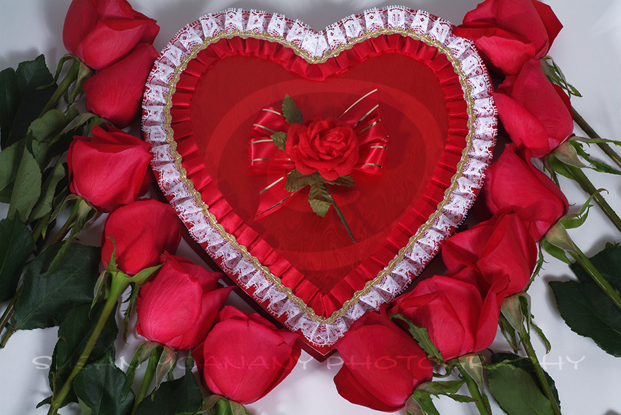 image of heart shaped candy box surrounded with red roses